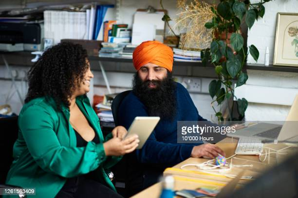 millennial colleagues using tablet in office - turban stock pictures, royalty-free photos & images