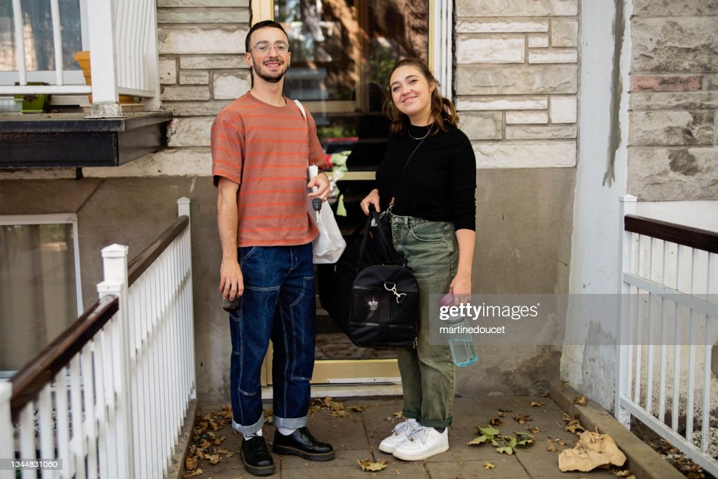 Millennial couple and newly adopted kitten in pet carrier at home. : Stock Photo