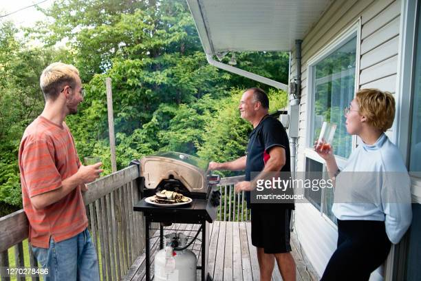 """millennial couple and senior man with barbecue in country house. - """"martine doucet"""" or martinedoucet stock pictures, royalty-free photos & images"""