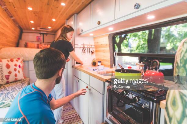 millennial couple cook breakfast in the van they live in - vehicle interior stock pictures, royalty-free photos & images
