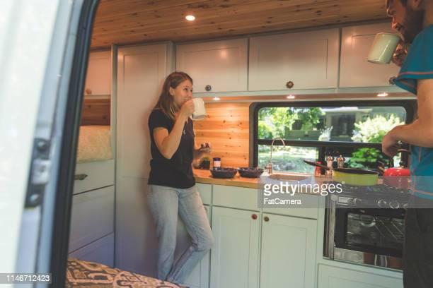 jahrtausende paar trinkt kaffee in dem van, in dem sie leben - wohngebäude innenansicht stock-fotos und bilder