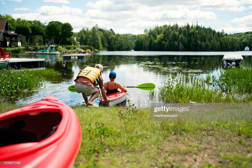 Millennial couple going kayaking on country lake. : Stock Photo