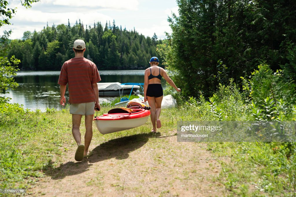 Millennial couple going kayaking on country lake. : Stock Photo