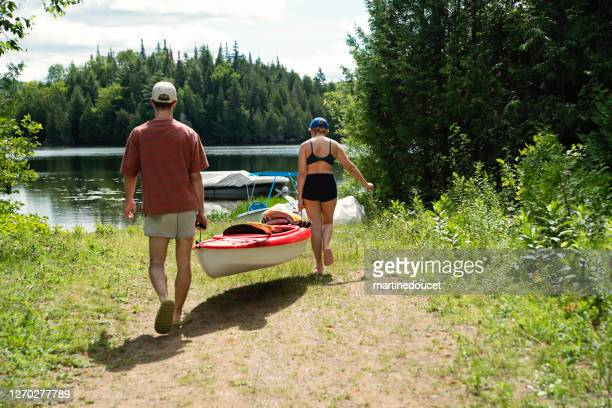 """millennial couple going kayaking on country lake. - """"martine doucet"""" or martinedoucet stock pictures, royalty-free photos & images"""