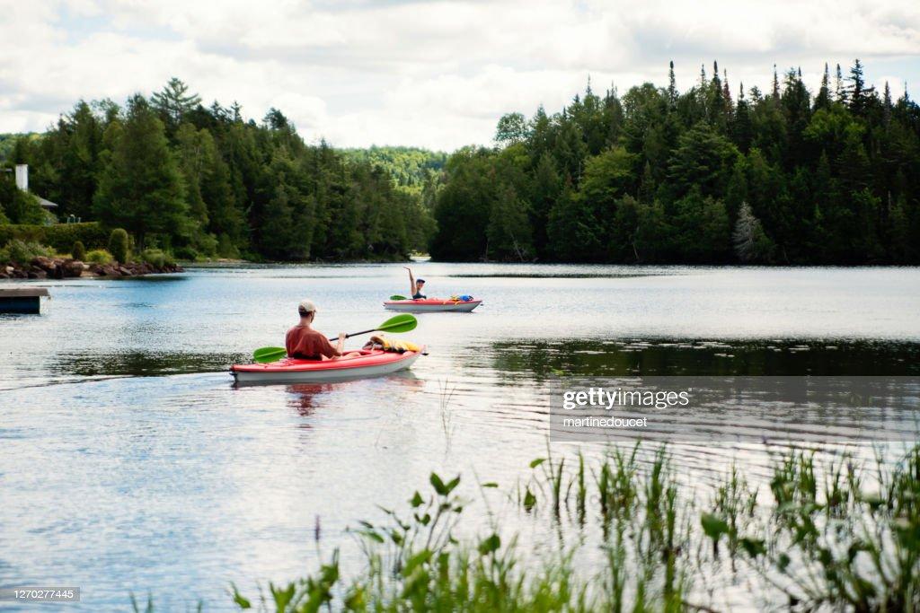 Millennial couple kayaking on country lake. : Stock Photo