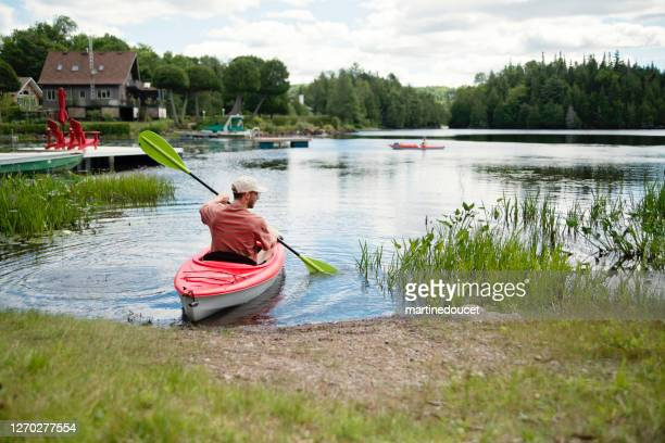 """millennial couple kayaking on country lake. - """"martine doucet"""" or martinedoucet stock pictures, royalty-free photos & images"""