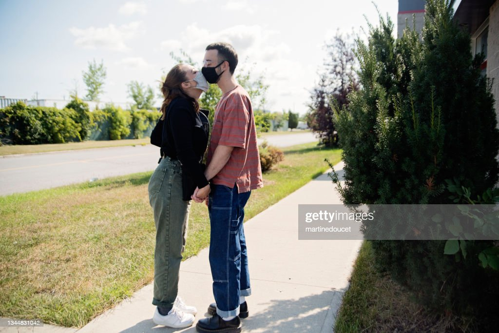 Millennial couple kissing with mask on the street. : Stock Photo