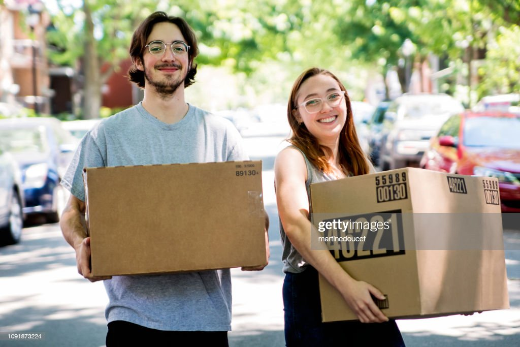Millennial couple moving in new apartment. : Stock Photo