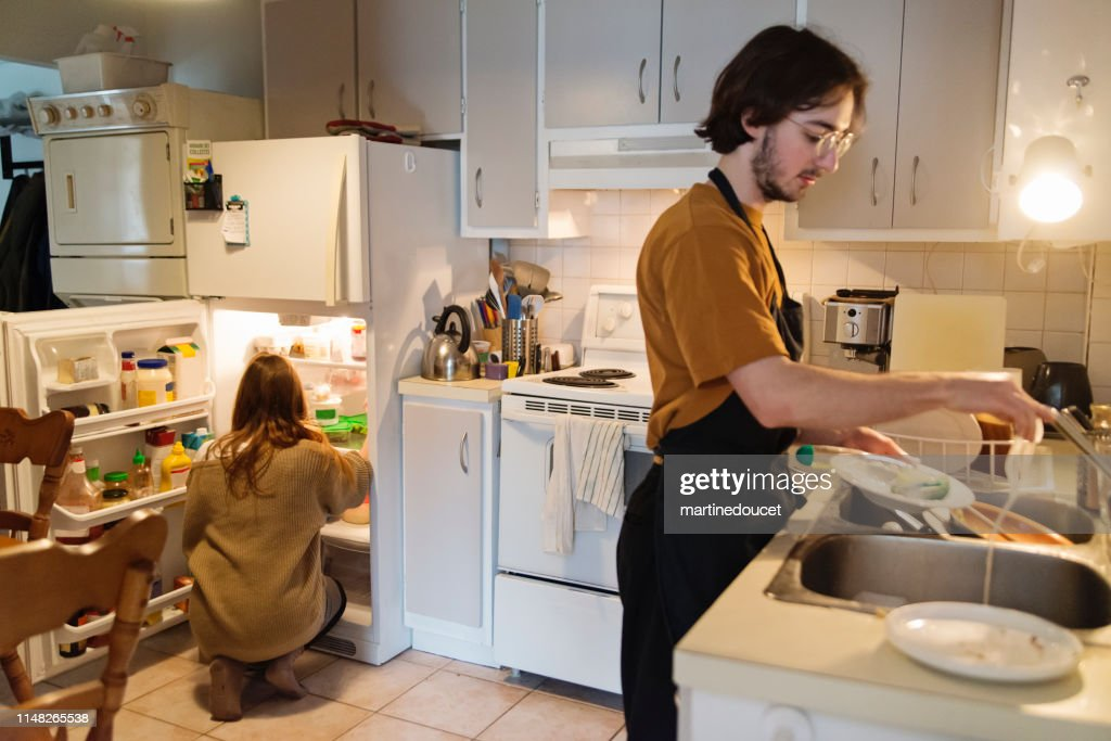 Millennial couple of students shared living doing chores. : Stock Photo