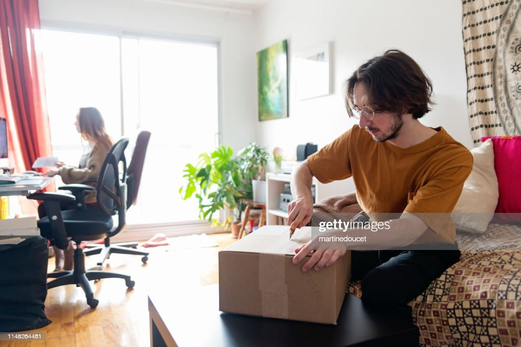Millennial couple opening a delivered package in living room. : Stock Photo