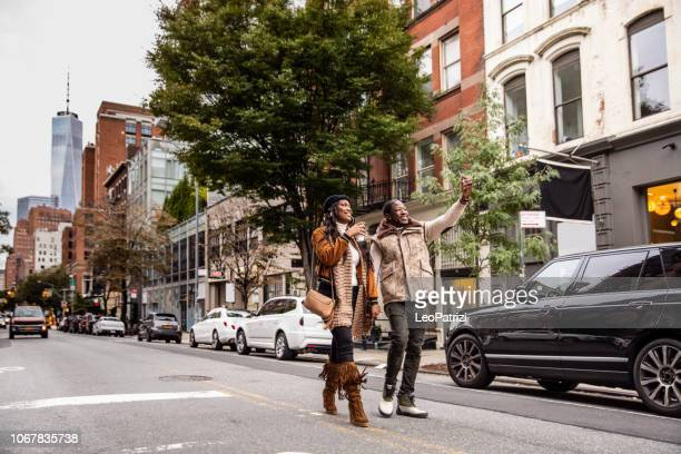 millennial couple walking in soho - new york - soho new york stock photos and pictures