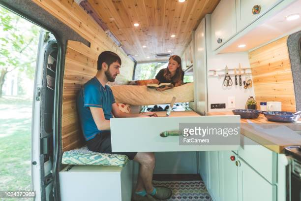 Millennial couple working and reading in the van they live in