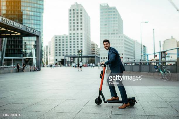 millennial employee in full suit on electric scooter going to work - northern european stock pictures, royalty-free photos & images