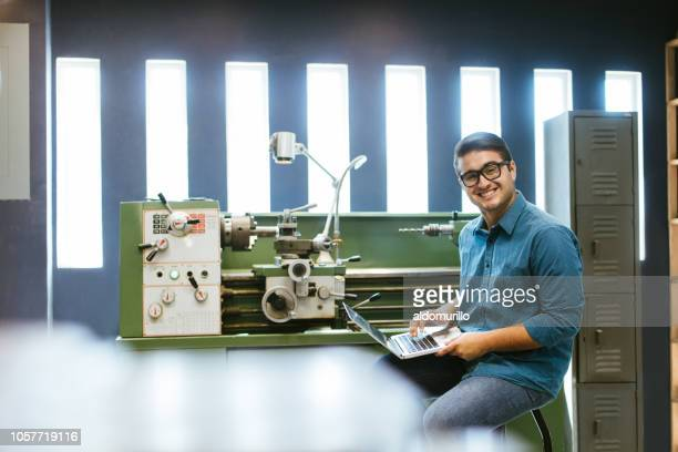 Millennial engineer working on laptop in shop