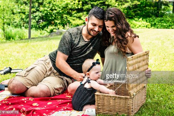 Millennial family having a picnic outdoors in summer.