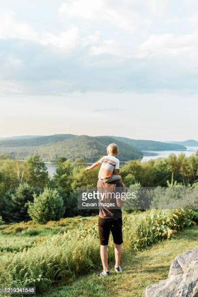 millennial father and his son exploring a park in massachusetts. - reservoir stock pictures, royalty-free photos & images