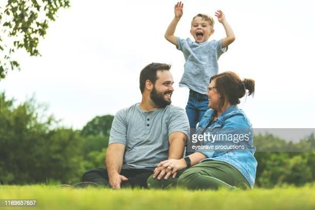 pai e matriz millennial com a criança autista no parque verde luxúria público que senta-se no pose de sorriso da grama para o retrato da família - autismo - fotografias e filmes do acervo