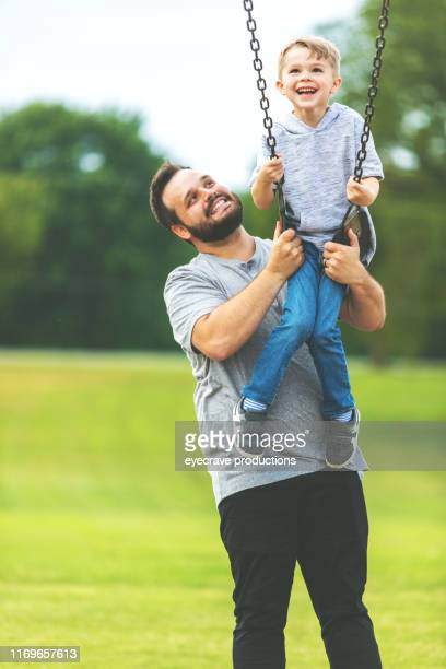 Millennial father playing with son swinging on swingset at a public park Playground having fun together