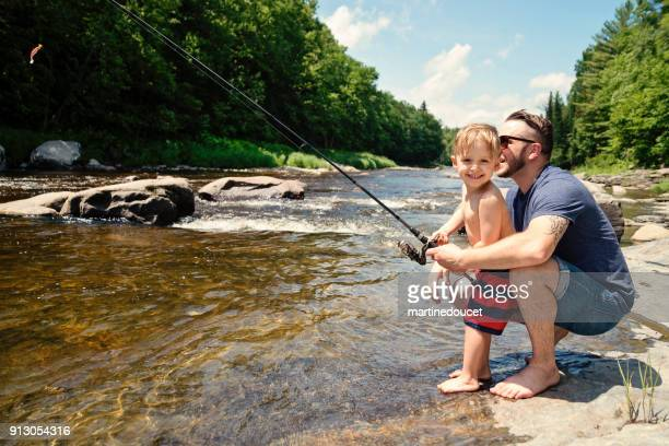 Millennial father showing son how to fish in a river in summer nature.