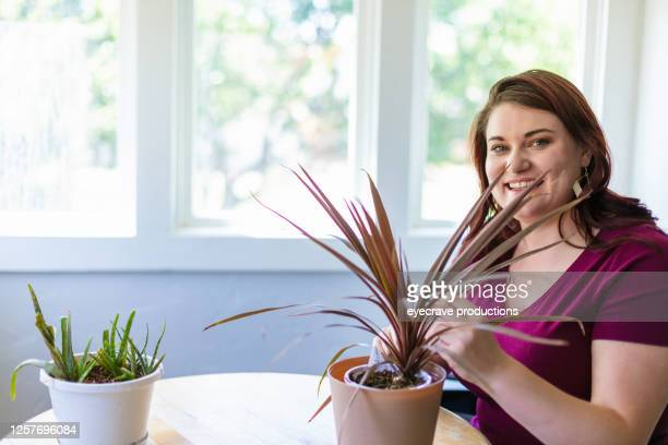 millennial female caring for two potted plants on a bistro table with wood top - eyecrave  stock pictures, royalty-free photos & images