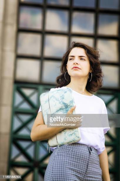 millennial female college students holding a tablet bag, looking away thoughtful - monday stock pictures, royalty-free photos & images