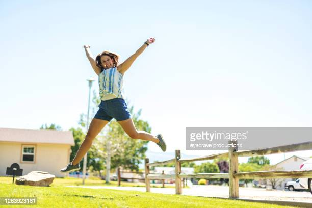 millennial female jumping for joy - eyecrave  stock pictures, royalty-free photos & images