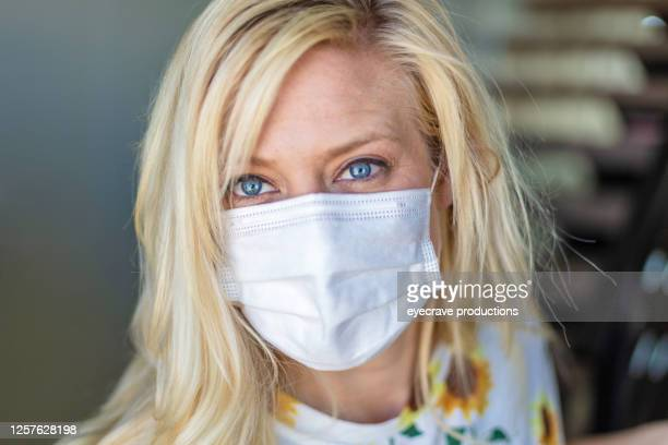 millennial female wearing face mask as walks out the front door of residence - eyecrave  stock pictures, royalty-free photos & images