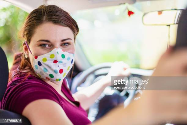 millennial female wearing face mask in car backing up in car - eyecrave  stock pictures, royalty-free photos & images