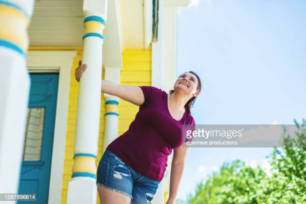 millennial female with reddish brown hair color holding onto front porch decorative post - eyecrave  stock pictures, royalty-free photos & images