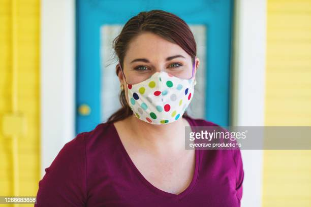 millennial female with reddish brown hair color on front porch with face mask - eyecrave  stock pictures, royalty-free photos & images