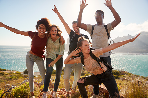 Millennial friends on a hiking trip celebrate reaching the summit and have fun posing for photos 1162739206