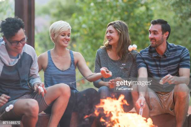 millennial friends roasting smores by the fire - couple chocolate stock pictures, royalty-free photos & images