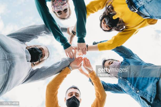 millennial friends stacking hands together - view from below - five people stock pictures, royalty-free photos & images