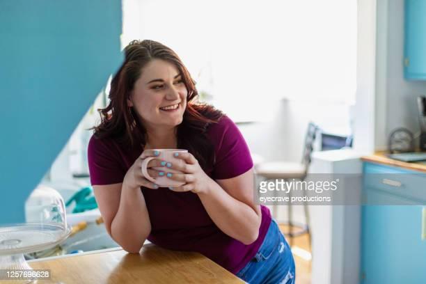 millennial generation female enjoying hot beverage in kitchen - eyecrave  stock pictures, royalty-free photos & images