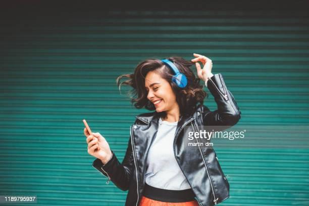 ragazza millenaria che si gode la musica da discoteca - giacca di pelle foto e immagini stock