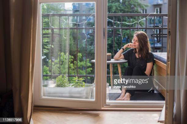 millennial girl sits on a balcony - apartment balcony stock pictures, royalty-free photos & images
