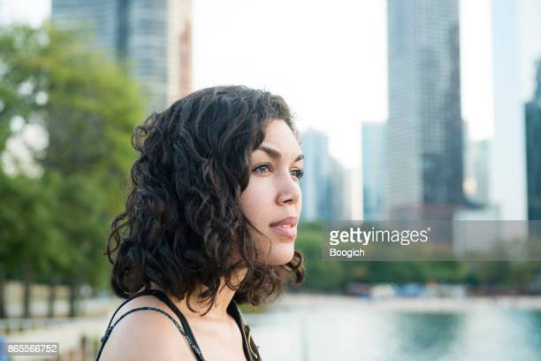 Millennial Hispanic Woman by Chicago Skyline in Contemplation