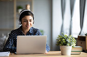 Millennial Indian girl in headphones using laptop at home