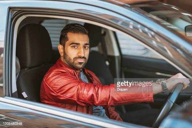 millennial indian man driving crowdsourced taxi - asian stock pictures, royalty-free photos & images