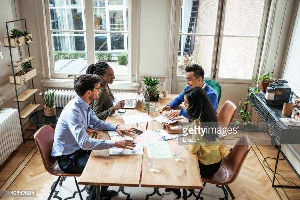 millennial investors planning to develop crowdfunded project in modern office. - employee engagement stock pictures, royalty-free photos & images