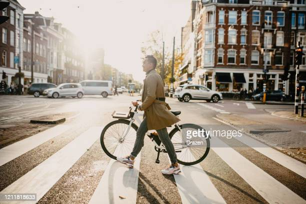 millennial japanese commuter in the city with bicycle, crossing the street - amsterdam stock pictures, royalty-free photos & images