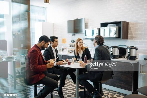 millennial latin coworkers taking a break at work, eating snack and chatting. - canteen stock pictures, royalty-free photos & images