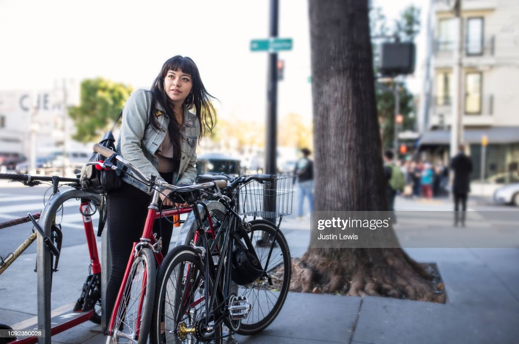 Millennial Latina Bicycle Commuting, Locking Her Bike on City Sidewalk : Stock Photo
