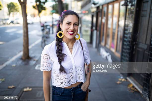 millennial latina stands alone on city sidewalk, smiling and looking at camera, wearing white lace blouse and bright yellow hoop earrings - mid adult stock-fotos und bilder
