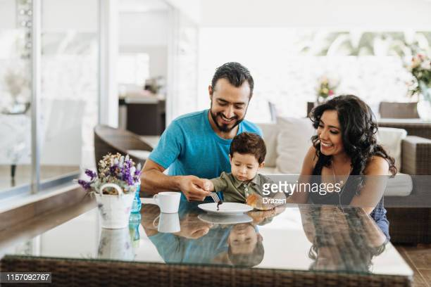 millennial latino parents with toddler. - mexican ethnicity stock pictures, royalty-free photos & images
