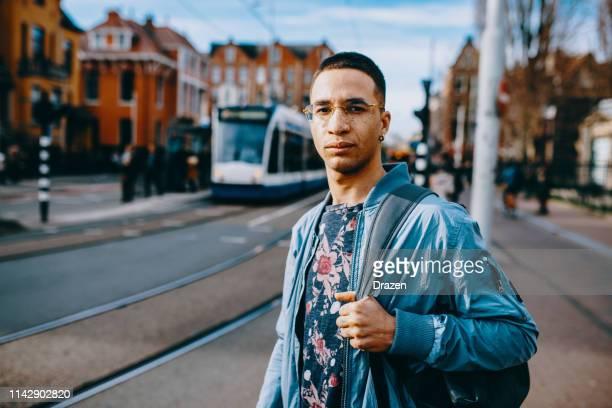 duizendjarige latino student die in europa woont en gebruik maakt van het openbaar vervoer. - nederlandse cultuur stockfoto's en -beelden