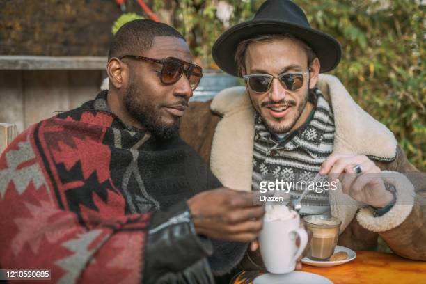 millennial lgbt couple on city break - drinking coffee and laughing - downtown comedy duo stock pictures, royalty-free photos & images