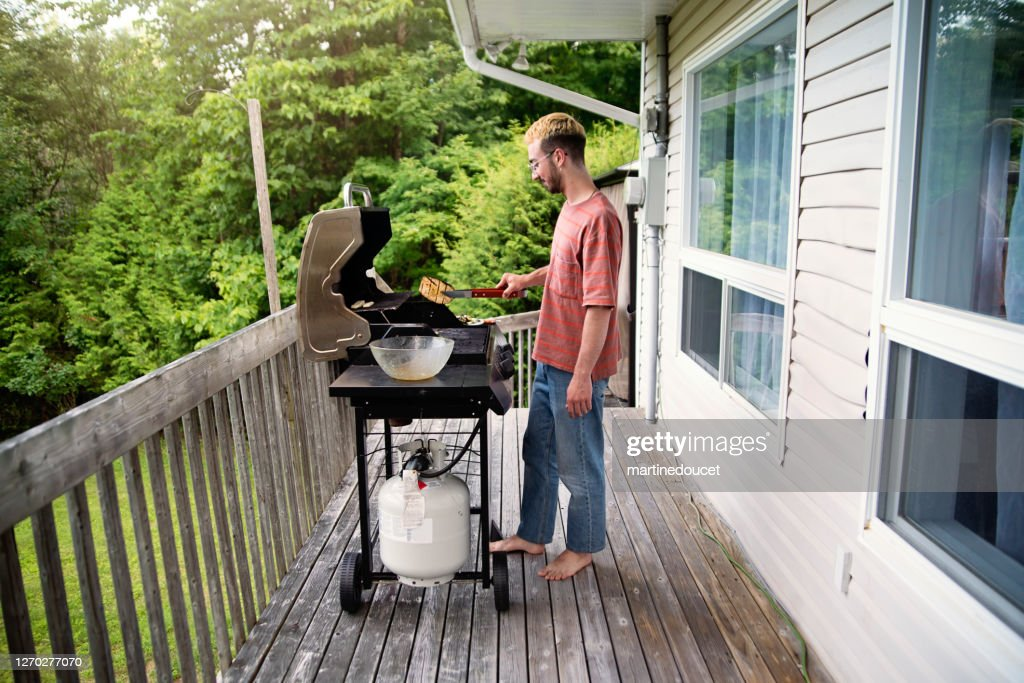 Millennial man cooking vegetables on barbecue in country house. : Stock Photo