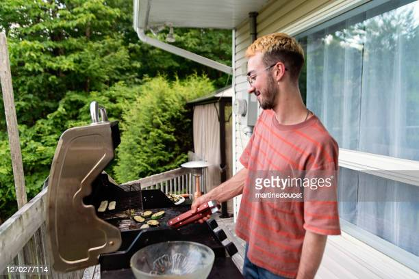 """millennial man cooking vegetables on barbecue in country house. - """"martine doucet"""" or martinedoucet stock pictures, royalty-free photos & images"""