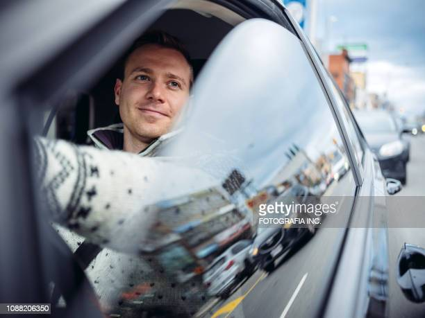 millennial man driving in a car in winter - driver stock pictures, royalty-free photos & images